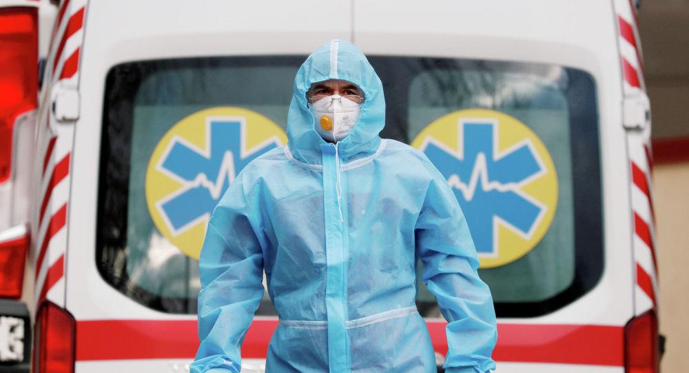 Медицинский работник в защитном костюме стоит рядом с машиной скорой помощи. Архивное фото
