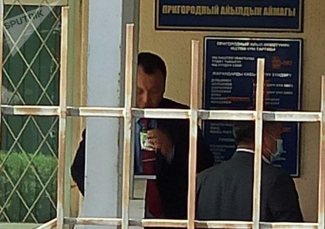 Чиновник с кофе возле захваченного женщинами здания айыл окмоту в селе Пригородное. 15 апреля 2021 года