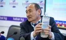 Министр здравоохранения Алымкадыр Бейшеналиев показывает бутылку с настойкой иссык-кульского корня. Архивное фото