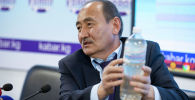 Министр здравоохранения Алымкадыр Бейшеналиев показывает бутылку с настойкой иссык-кульского корня