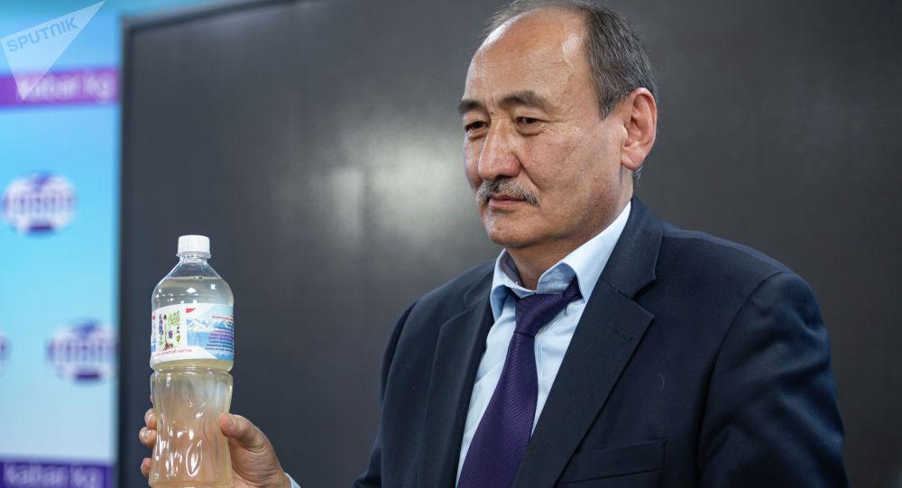 Министр здравоохранения Алымкадыр Бейшеналиев показывает бутылку настойки иссык-кульского корня (ядовитое растение) на пресс-конференции в Бишкеке