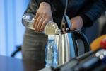 Мужчина наливает в чайник бутылку настойки иссык-кульского корня. Архивное фото