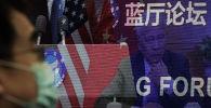 Мужчина в маске, помогающей сдержать распространение коронавируса, сидит возле экрана, демонстрирующего, как делегаты присутствуют на форуме Лантинга, посвященном приезду Китая и США. отношения вернулись в правильное русло, которое под председательством министра иностранных дел Китая Ван И в офисе Министерства иностранных дел в Пекине в понедельник, 22 февраля 2021 года.