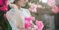 Девушка с цветами во время фотосессии. Иллюстративное фото