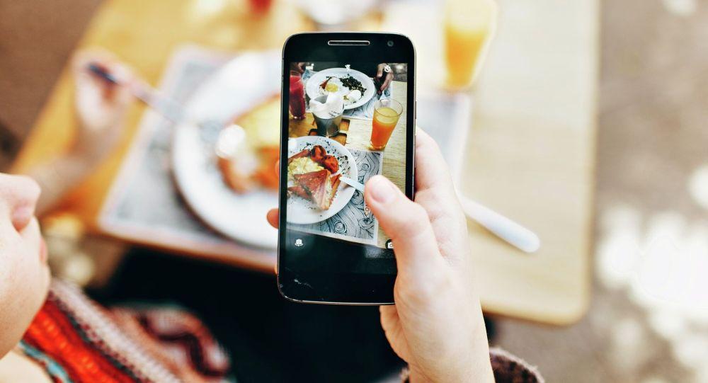 Девушка фотографирует свое блюдо. Иллюстративное фото