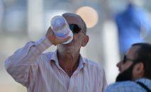 Мужчина пьет воду из бутылки. Архивное фото