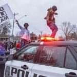 АКШнын Бруклин-Сентер шаарынын борборунда өткөн нааразычылык акциясынын катышуучулары полициянын унаасынын капотуна чыгып алышкан. 11-апрелде полиция кыз электрошокердин ордуна тапанчаны алмаштырып алып, кармоо учурунда каршылык көрсөткөн афроамерикалык жаранды атып салган. Бул окуяга нааразы болгондор көчөгө чыгышкан. Миннеаполистин мэри өзгөчө абал жана коменданттык саат киргизилгенин жар салды