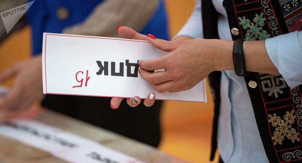 Шайлоо комиссиянын кызматкери НДПК партиянын табличкасы менен. Архив