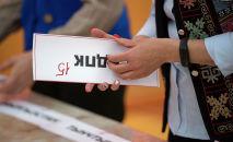 Шайлоо комиссиясынын кызматкери КЭДП партиясынын табличкасын кармап турат