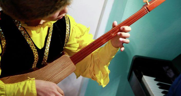 Ученица Сокулукской музыкальной школы Адинай Жумакадыровой играет на подаренном от имени президента комузе. 20 апреля 2021 года