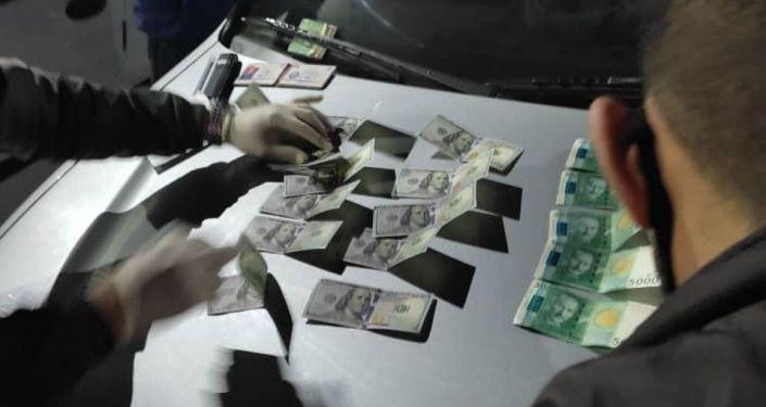 Сотрудники МВД КР при изъятии взятки у подозреваемых в вымогательстве. 21 апреля 2021 года