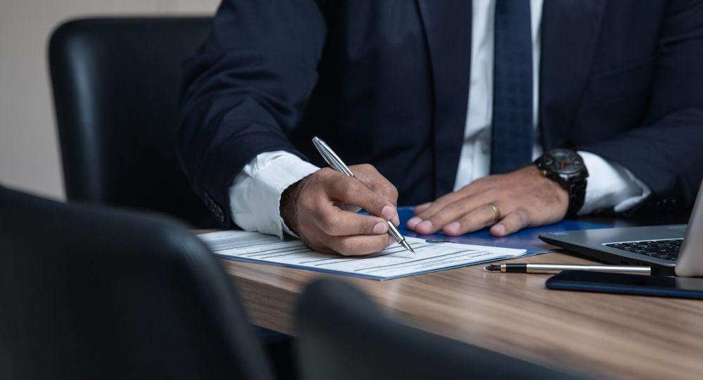 Мужчина подписывает документ. Иллюстративное фото