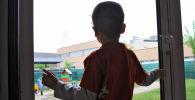 Ребенок смотрит в окно. Архивное фото
