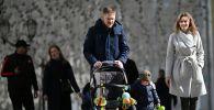 Молодые люди с ребёнком во время прогулки на улице Никольская в Москве.