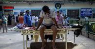 Пациент с COVID-19 ожидает госпитализации у отделения скорой помощи в больнице в Нью-Дели