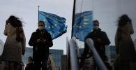 Люди в защитных масках на фоне флагов Евросоюза. Архивное фото