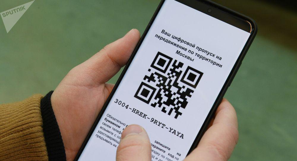 Киши телефонунда QR-кодду карап жатат. Архив
