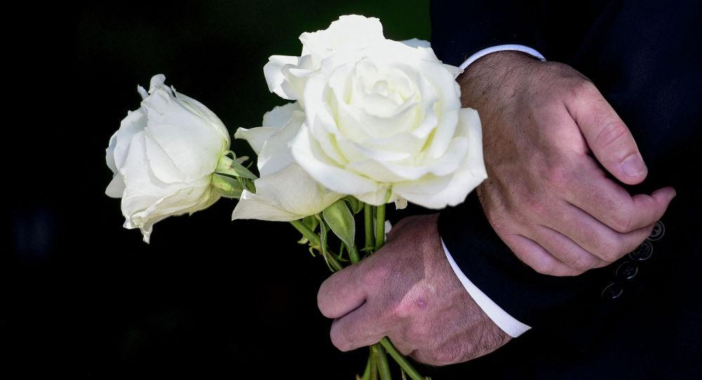 Мужчина держит цветы на похоронах. Архивное фото