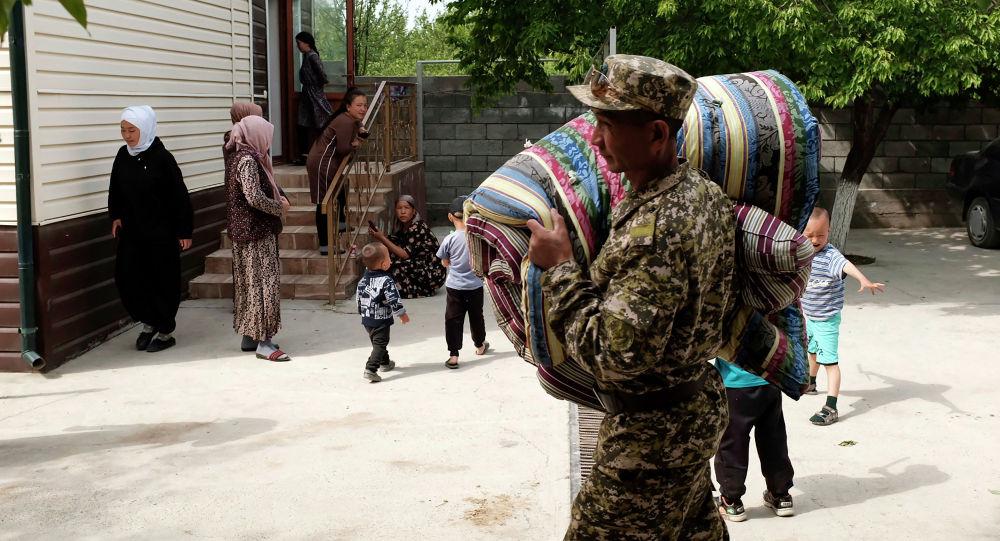 Военнослужащий МЧС Кыргызстана несет матрасы для граждан, которые были эвакуированы из районов, граничащих с Таджикистаном