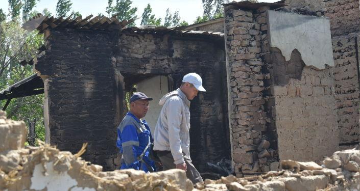 Люди в сгоревшем здании в селе Максат, после конфликта с Таджикистаном