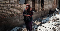 Баткен облусундагы талкаланган үйүнүн жанында турган аял. Архив
