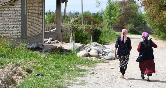 Местные жители идут по улице в одном сел Лейлекского района, после приграничного конфликта между Кыргызстаном и Таджикистаном