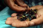 Торговец держит пригоршню драгоценных камней. Архивное фото