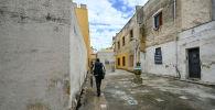 Сицилия провинциясында киши көчөдө бара жатат. Архив