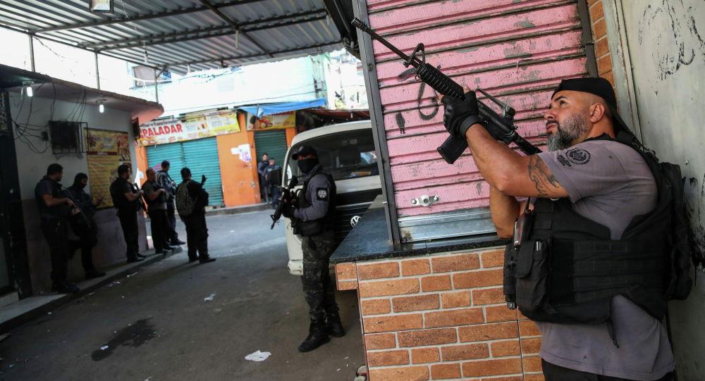 Полицейские стоят на позиции во время операции против торговцев наркотиками в трущобах в Рио-де-Жанейро (Бразилия)