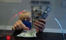 Сотрудник банка считает доллары США. Архивное фото