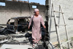 Женщина стоит у сгоревшего строения в приграничном с Таджикистаном селе Максат Лейлекского района Баткенской области.