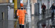 Сотрудник коммунальной службы убирает улицу в Москве. Архивное фото