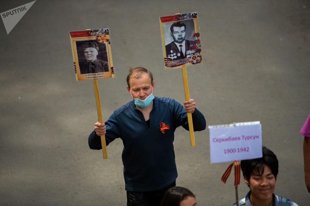Около 50 человек с портретами ветеранов прошли от Южных ворот до Вечного огня на площади Победы по тротуару улицы Байтик Баатыра (Абдрахманова)
