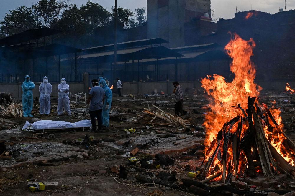 Родственники стоят возле тела человека, умершего из-за коронавируса Covid-19, на месте кремации в Нью-Дели, Индия. 6 мая 2021 года