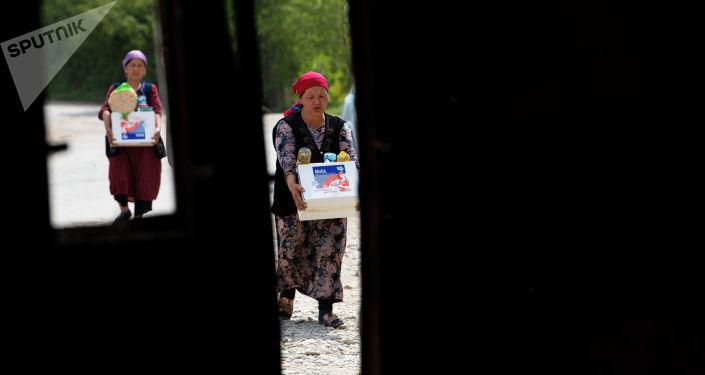 Жители одного из сел Лейлекского района несут гуманитарную помощь после приграничного конфликта между Кыргызстаном и Таджикистаном