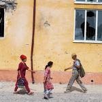 Жители села Максат Лейлекского района возле школы, сгоревшей в ходе приграничного конфликта между Кыргызстаном и Таджикистаном