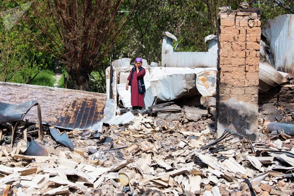 Жительница села Максат Лейлекского района возле своего дома, сгоревшего в ходе приграничного конфликта между Кыргызстаном и Таджикистаном