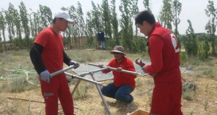 Сотрудники Красного Креста помогают провести воду жителям села Максат, которые потеряли свои дома после военного конфликта на кыргызско-таджикской границе