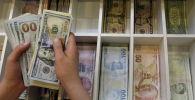 Сотрудник обменки считает доллары США. Архивное фото