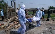 Родственники в СИЗах несут труп человека, умершего от COVID-19 в Морадабаде (Индия)