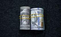 Пачка стодолларовых и тысячесомовых купюр. Иллюстративное фото