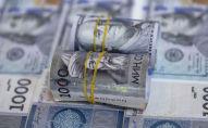 Пачка стодолларовых и тысячесомовых купюр на столе. Иллюстративное фото