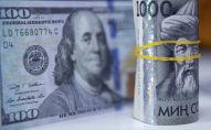 Пачка сто долларовых и тысяча сомовых купюр. Иллюстративное фото