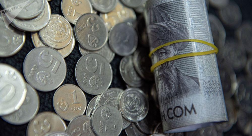 Пачка тысячесомовых купюр и монеты на полу. Иллюстративное фото