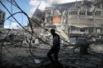 Израилдин аба соккусунан кыйраган имараттардын жанынан палестиналык киши өтүп бара жатат