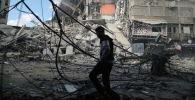Палестинец проходит мимо разрушенных зданий в результате израильских воздушных ударов