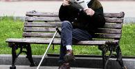 Мужчина читает газету сидя на лавочке. Архивное фото