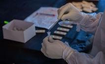 Медицинский работник берет образцы мазков у людей на COVID-19