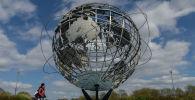 Мальчик проезжает на велосипеде мимо сферического изображения Земли в Нью-Йорке. Архивное фото