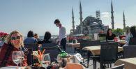 Туристтер Стамбулдагы Айя София мечитинин жанында отурат